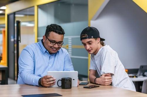 Deux personnes assises face à une tablette